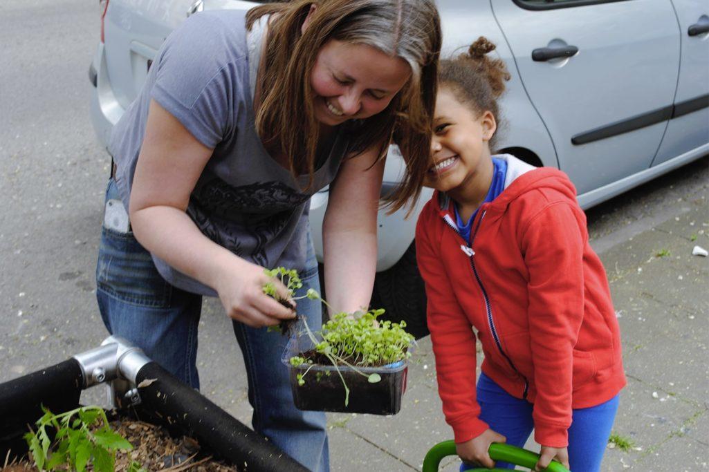 maman et enfant rient en jardinant